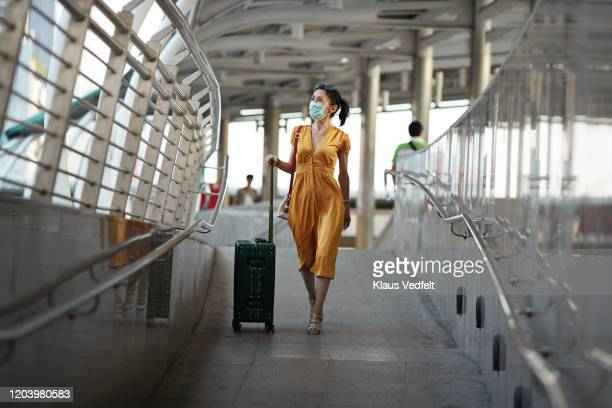 woman walking with luggage at railroad station - travel foto e immagini stock