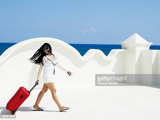 Woman walking with luggage on patio of resort