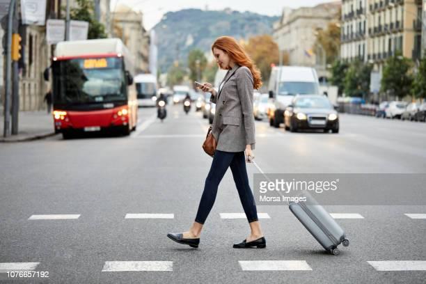 mujer caminando con maletas en la calle usar teléfono - cruzar fotografías e imágenes de stock