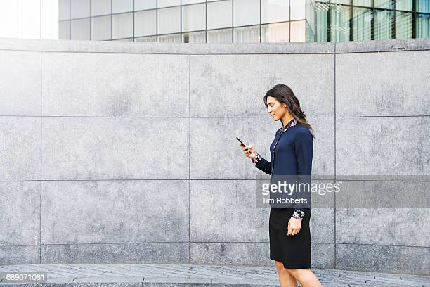 woman walking with mobile - gray skirt stock pictures, royalty-free photos & images
