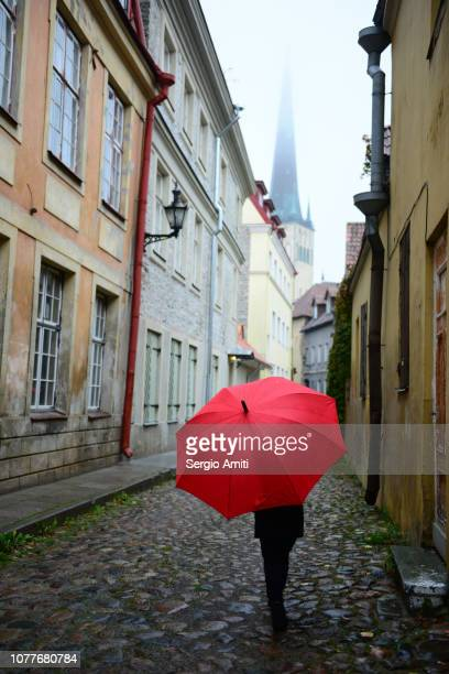 Woman walking with red umbrella