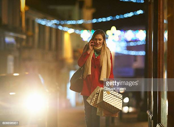 Woman walking with shopping and using phone.
