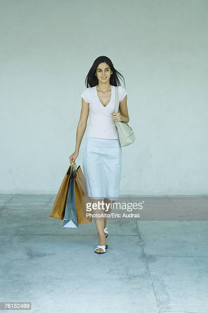 """""""woman walking with shopping bags, full length"""" - long purse stock photos and pictures"""