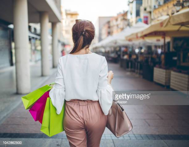 woman walking with shopping bags. shot from behind. - beautiful female bottoms stock pictures, royalty-free photos & images