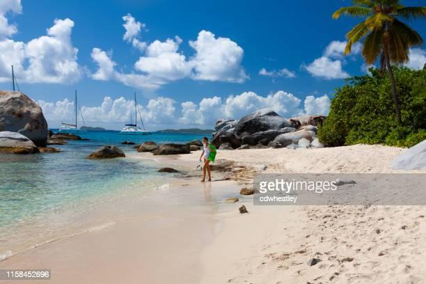 mujer caminando con equipo de snorkel en la playa, los baños, gorda virgen - islas de virgin gorda fotografías e imágenes de stock