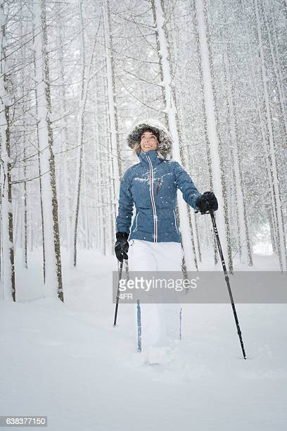 Woman walking with Snowshoes through a Winter Forest