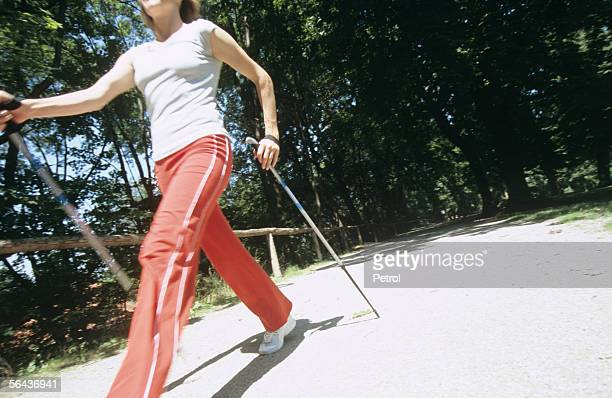 Woman walking with sticks, nordic walking
