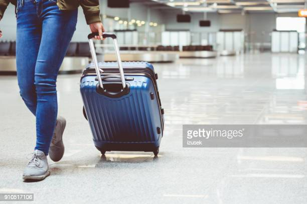 woman walking with suitcase at airport terminal - baggage claim stock pictures, royalty-free photos & images