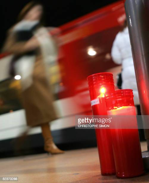 A woman walks 11 March 2005 behind candles lite on the platform 2 at the Atocha railway station in memory of the victims of the 11 March 2004 train...