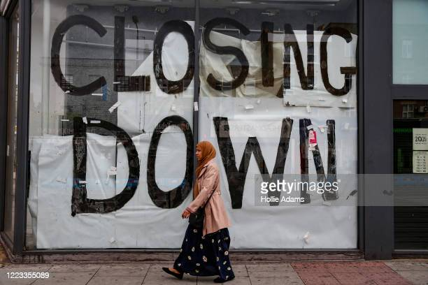 Woman walks a boarded up shop in Camden on June 28, 2020 in London, England. More retailers are reopening with social distancing measures after being...