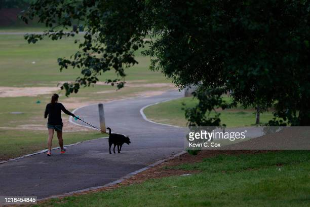Woman walks a dog on a trail through Piedmont Park, normally packed for Easter, on April 12, 2020 in Atlanta, Georgia. With the exception of...