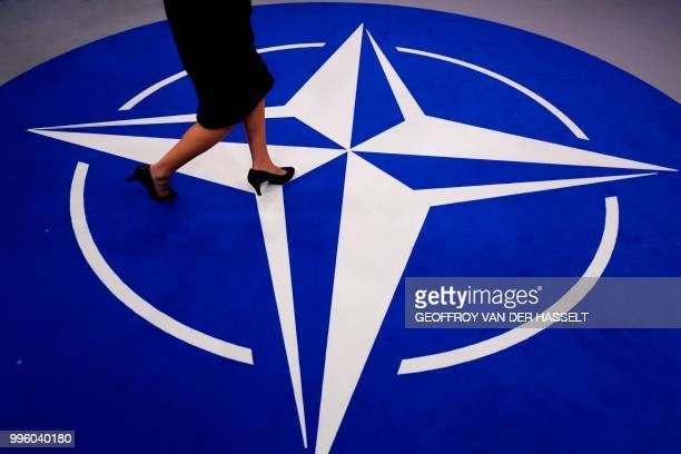Woman walks across a carpet with the NATO logo ahead of the NATO summit, at the NATO headquarters in Brussels, on July 11, 2018.
