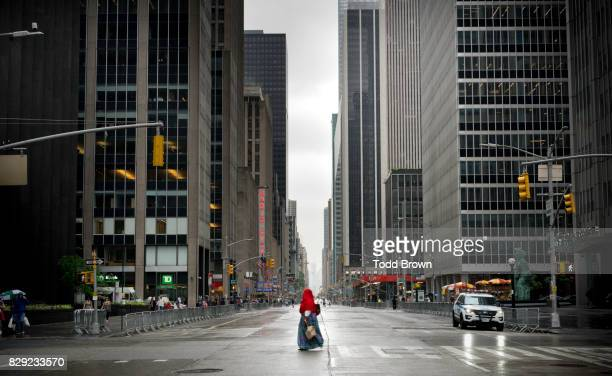 woman walks across an empty 6th Avenue in NYC