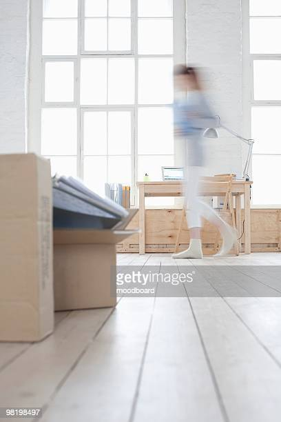 Woman walks across loft apartment, blurred motion