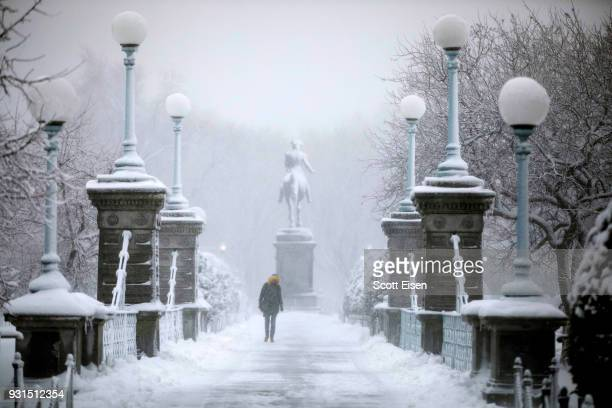 A woman walks across the Boston Public Garden Bridge as Winter Storm Skylar bears down on March 13 2018 in Boston Massachusetts This is the third...