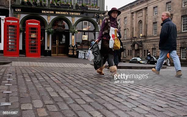Woman walks across the cobblestones on the Royal Mile on January 9 Edinburgh Scotland. The granite cobbles on the Royal Mile will start to be lifted...