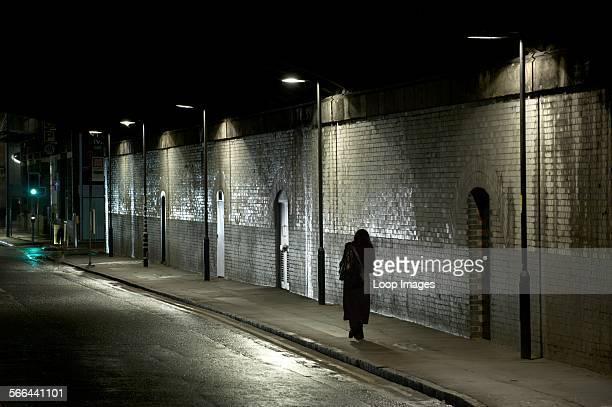 Woman walks alone beneath a dark tunnel in Manchester.