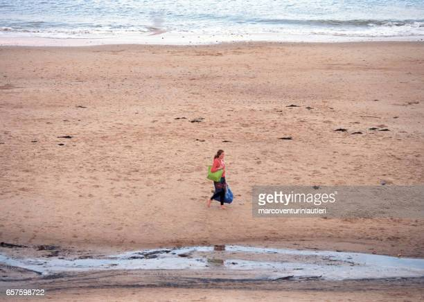 Woman walks alone on the empty beach