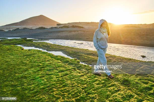 Woman walks alone on the rocks with colorful seaweed at the beach on January 19 2018 in El Medano Tenerife Spain Model released