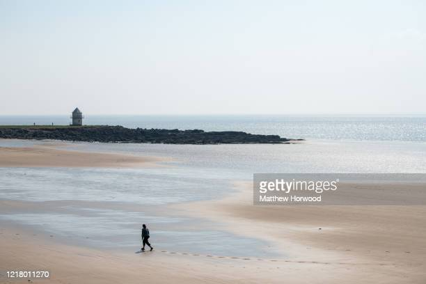 A woman walks alone on Trecco Bay beach on April 10 2020 in Porthcawl United Kingdom Police have stepped up patrols to prevent people from travelling...