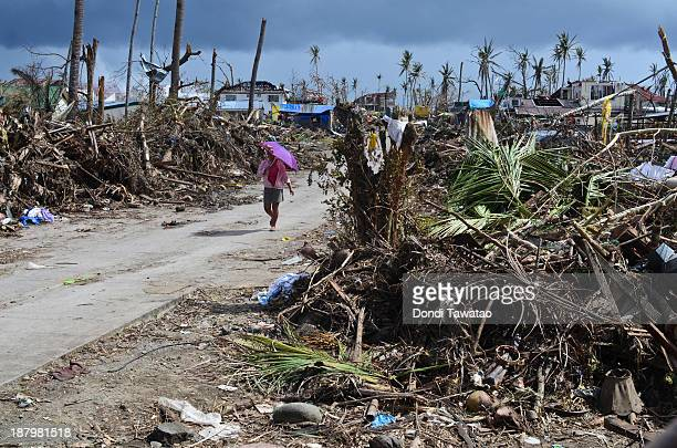 A woman walks along a devastated area in Tacloban City on November 14 2013 in Tacloban Philippines Typhoon Haiyan which ripped through Philippines...