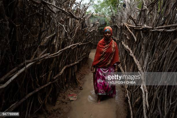 Woman walks along a flooded path between shelters after a heavy rainy season downpour at the Dadaab refugee complex, in the north-east of Kenya, on...