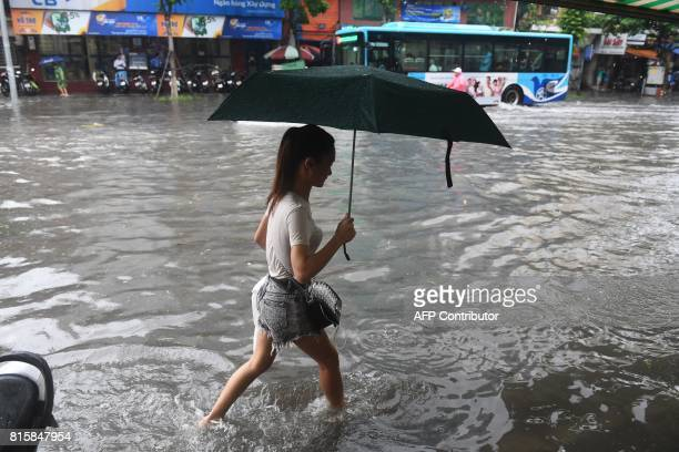 A woman walks along a flooded street in Hanoi on July 17 after tropical storm Talas made landfall in northern Vietnam / AFP PHOTO / HOANG DINH NAM