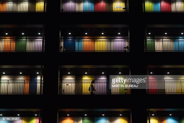TOPSHOT A woman walks along a passageway past appartements at a building in Tokyo on June 19 2018