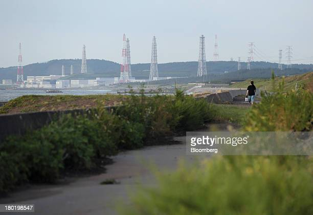 A woman walks along a path towards Tokyo Electric Power Co's Kashiwazaki Kariwa nuclear power station in Kashiwazaki City Niigata Prefecture Japan on...