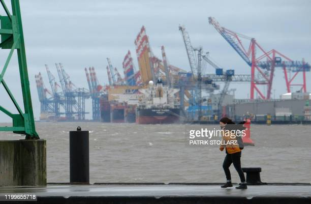 A woman walks along a seawall at the North Sea in Bremerhaven northern Germany on Febuary 9 2020 The storm named Sabine is estimated arriving along...