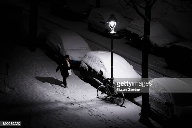 A woman walks along a snowcovered pavement on December 10 2017 in Berlin Germany