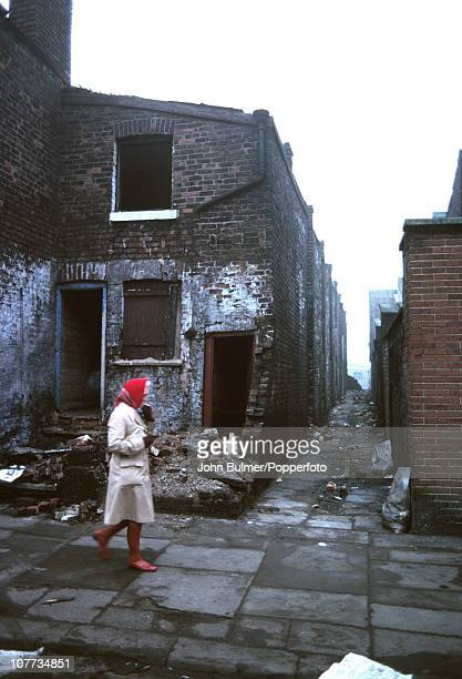 A woman walks along a street of derelict houses in Salford Greater Manchester England in 1976