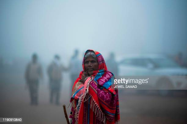 TOPSHOT A woman walks along a street under heavy foggy conditions in New Delhi on December 30 2019