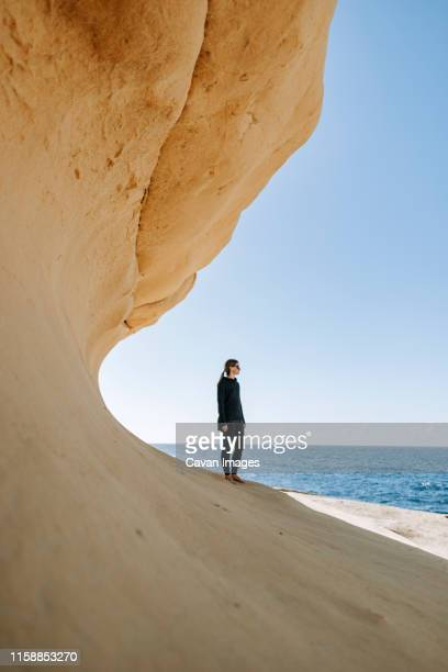 a woman walks along a striking rock formation on the island of malta - malta stock pictures, royalty-free photos & images