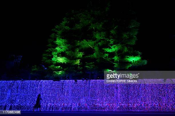 TOPSHOT A woman walks along a wall decorated with ornate lighting in front of a hotel where the New Zealand rugby team is putting up in Beppu on...
