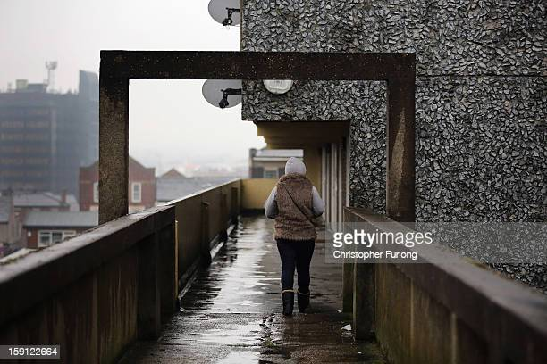 A woman walks along an elevated walkway on the Falinge Estate which has been surveyed as the most deprived area in England for a fifth year in a row...