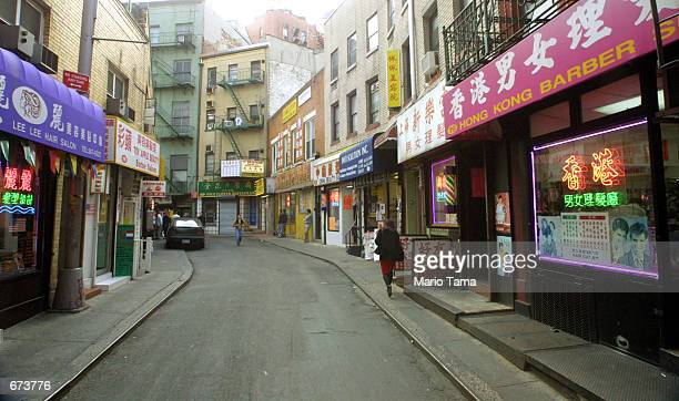 Woman walks along an empty street November 27, 2001 in the usually bustling Chinatown section of New York City. Chinatown is located in Lower...