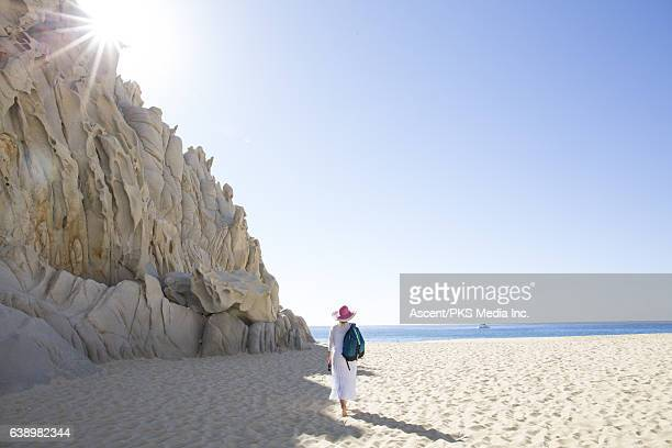 Woman walks along beach below rock cliffs