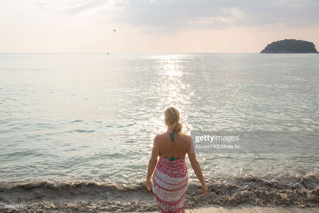 Woman walks along beach edge, looks out to sea : Stock Photo