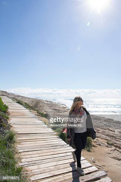 Woman walks along boardwalk, looks out to sea