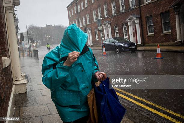 A woman walks along Bridge Street through heavy rain and hail on February 12 2014 in Worcester England The Environment Agency has issued flood...