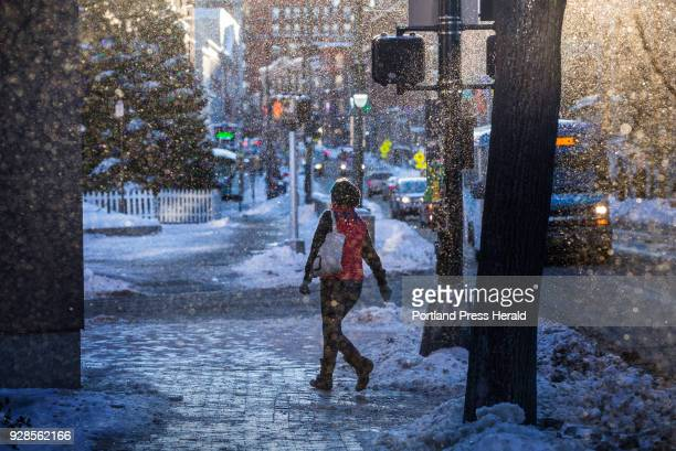 A woman walks along Congress Street on Tuesday Dec 26 as frozen particles blow through the air and are illuminated in late aternoon sun