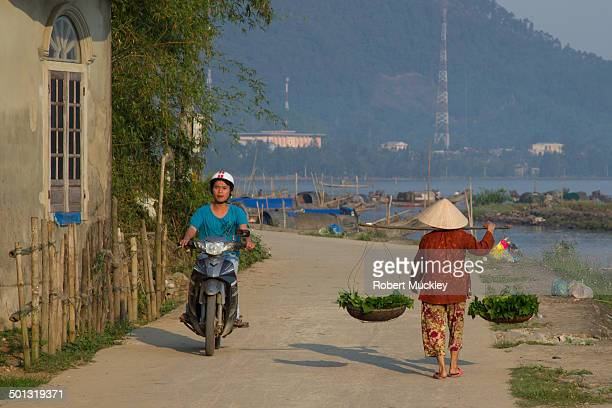 Woman walks along Fishing Village road away from camera wearing traditional clothes, Non La and carrying traditional yoke, while young man passes her...