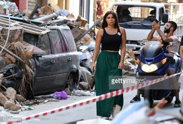 Woman walks along Gouraud street in Beirut as a man takes photographs on August 13 more than a week after a massive blast ravaged the port and parts...