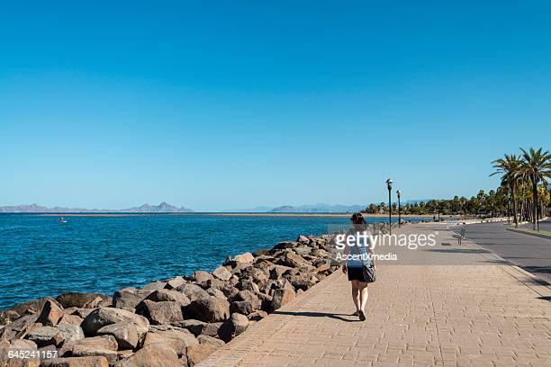 Woman walks along ocean promenade, uncrowded
