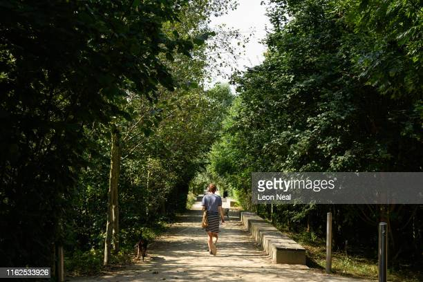 A woman walks along one of the many wooded boulevards within the Queen Elizabeth Olympic Park on July 17 2019 in London England On July 22 London...