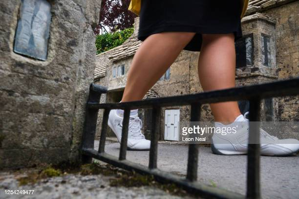 Woman walks along one of the miniature streets of the model village on July 04, 2020 in Bourton-on-the-Water, England. Model villages are among the...