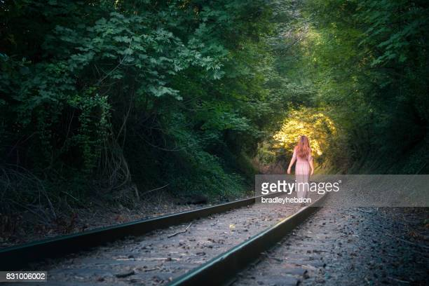 Woman walks along railroad tracks going towards the light