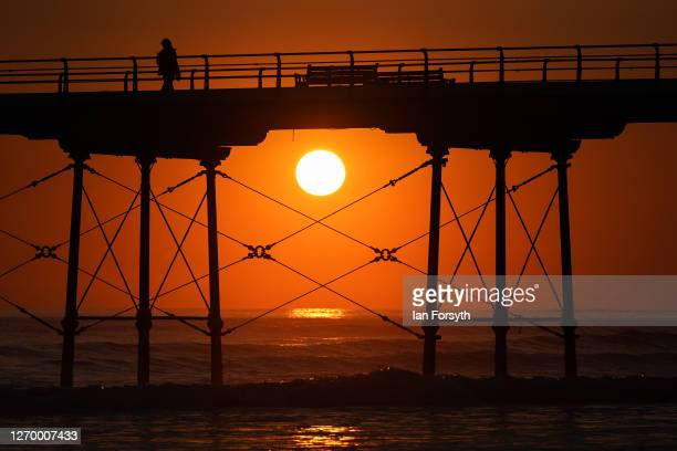 A woman walks along Saltburn pier at sunrise on September 01 2020 in Saltburn By The Sea England Today will be largely fine and dry for most today...