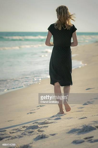 woman walks along the beach - donne bionde scalze foto e immagini stock